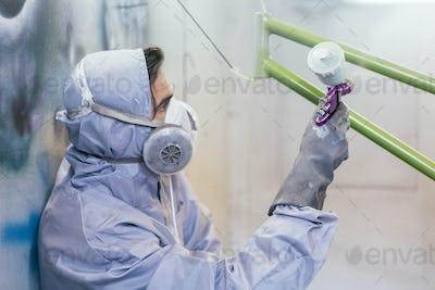 Man in respirator painting bike frame