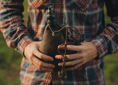 man holding a vintage leather water canteen