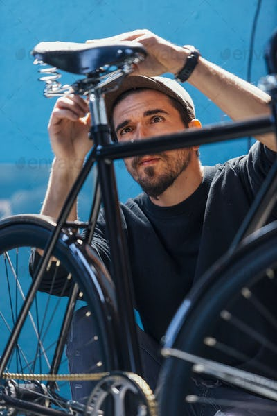 Close-up of man taking measurements of bicycle seat