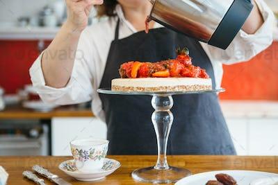 Woman decorating cake with strawberry jam