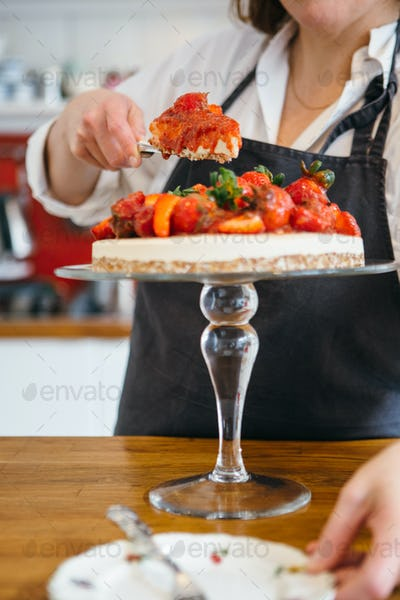Woman serving piece of pie on plate