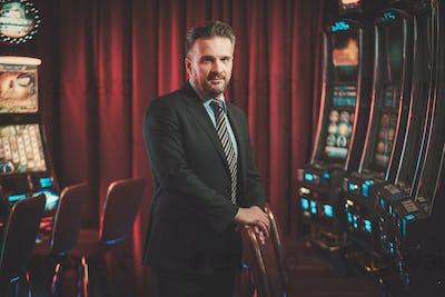 Elegant man near slots machines in a luxury casino interior