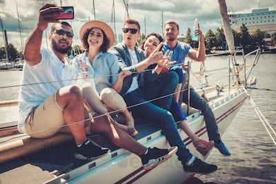 Happy friends taking selfie on a yacht