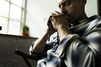 Cloesup of hands holding cross praying