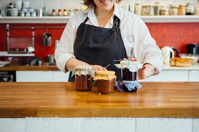 Smiling woman arranging jars of jam