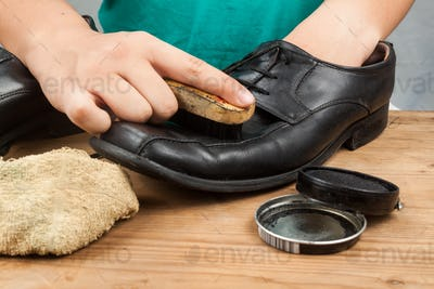 Person polishing and restoring worn out men's formal shoes