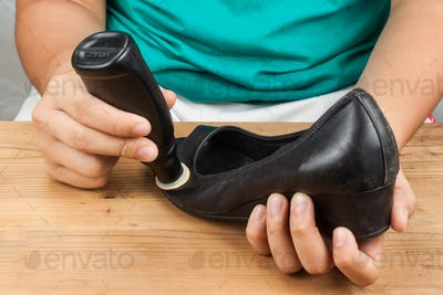 Person polishing and restoring worn out shoe with liquid shoe po