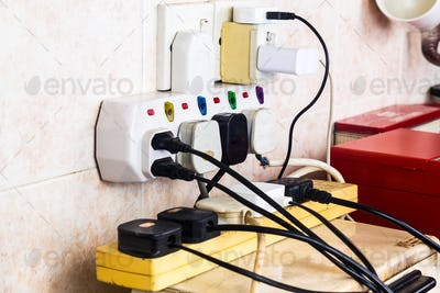 Multiple electricity plugs on adapter risk overloading and dange