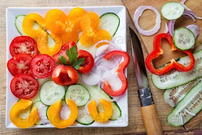 Salad of raw vegetables and ingredients with a knife