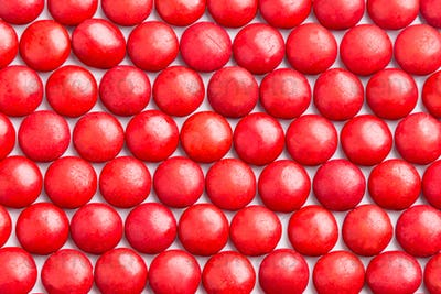 Close up neatly arranged red milk chocolate candies crisp shell