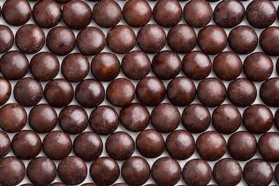 Close up neatly arranged brown milk chocolate candies crisp shel