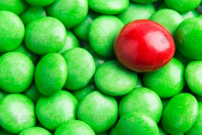 Focus on red chocolate candy against heaps of green candies
