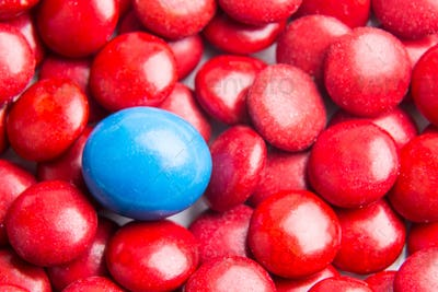 Focus on blue chocolate candy against heaps of red candies