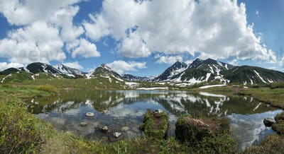 Panorama: Mountains, Mountain Lake and Clouds in Blue Sky on Sunny Day