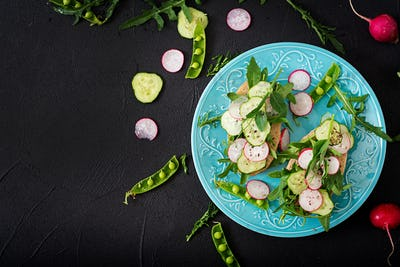 Vegetarian sandwiches with cucumber, radish, arugula and green peas. Flat lay. Top view
