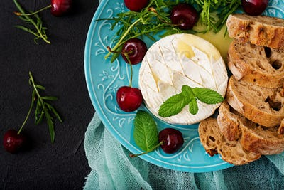 Baked Camembert cheese, toast and arugula salad with  sweet cherries. Flat lay. Top view