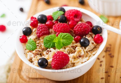 Tasty and healthy oatmeal porridge with berry, flax seeds and yogurt
