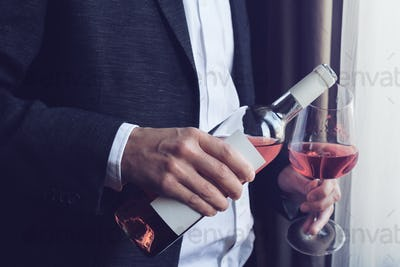 Man pouring rose wine into a glass