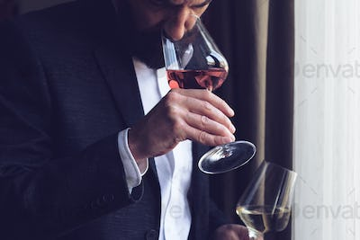 man tasting a glass of rose wine