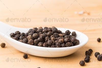 Spoonful of black pepper corns on wooden surface