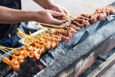 Vendor preparing chicken and beef barbecue satay on charcoal gri