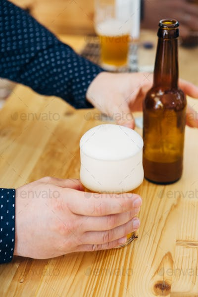 Unrecognizable man holding beer and bottle