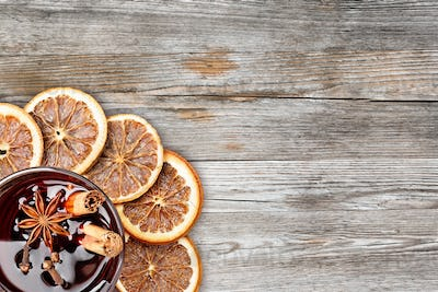 mulled wine and orange slices on rustic wooden background