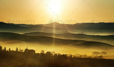 golden sunrise on the foggy countryside hills