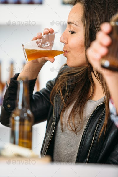 Side view of woman drinking beer