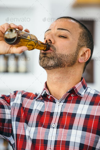 Man in checked shirt drinking beer