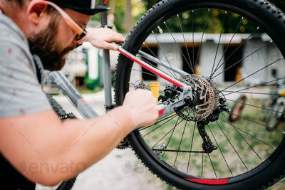 Bicycle mechanic adjusts back disk brakes
