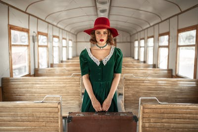 Woman with suitcase in retro train, old wagon