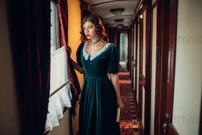 Woman in retro dress, vintage train compartment