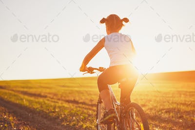 Girl enjoying bike ride at the sunset