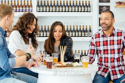 Company discussing beer at table