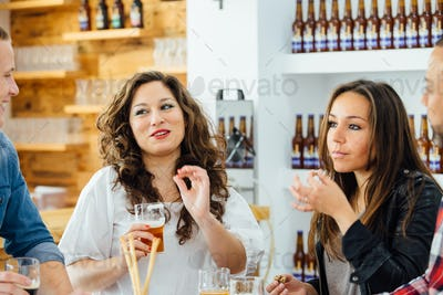 Four people eating at table with beer