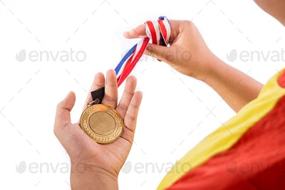 Athlete holding gold medal with ribbon on his hand