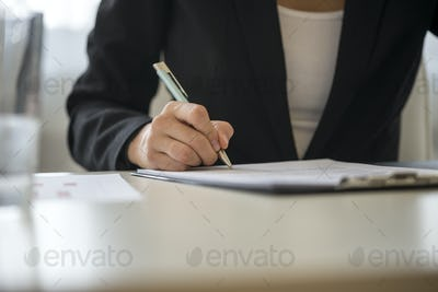 Low angle view of a woman signing contract