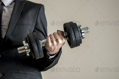 A businessman in business suit doing dumbbell biceps curl