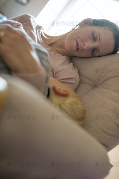 Young woman sleeping with a child in her arms