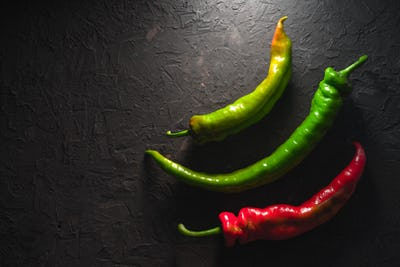 Multicolored chili pepper on a gray table