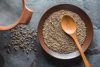 Hemp seeds on a plate, a sieve on a gray blue stone