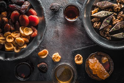 Dried fruits, nuts on a plate and tea on a gray slate close-up