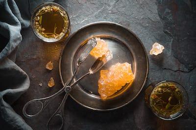 Grape sugar, tea and tongs on gray shale