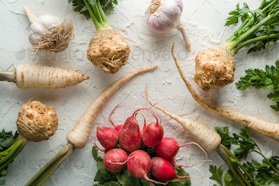 Background of celery roots, parsley, radishes with leaves and garlic on white table