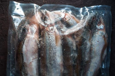 Background of frozen smelt in a vacuum package close-up