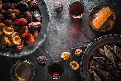 Dried fruits, grape sugar and tea on gray slate free space