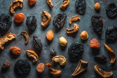 Dry dried apricots, figs and pears on a gray stone