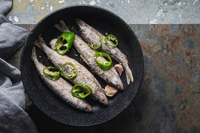 Fish, chili and garlic in a frying pan