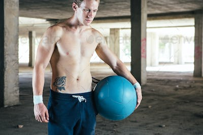 Man standing with weight ball in hand
